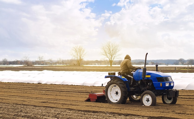 Rolnik na traktorze z frezarką spulchnia mieloną i miesza glebę