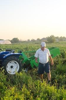 Rolnik naprzeciwko swojego traktora po zbiorach. wyciąg z warzyw korzeniowych
