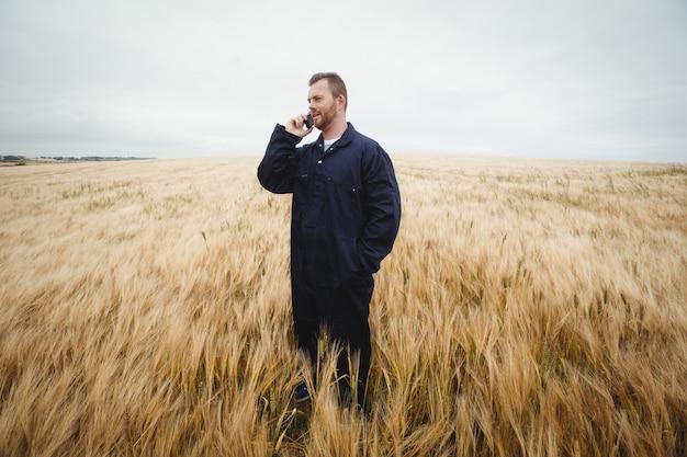 Rolnik opowiada na telefonie komórkowym w polu