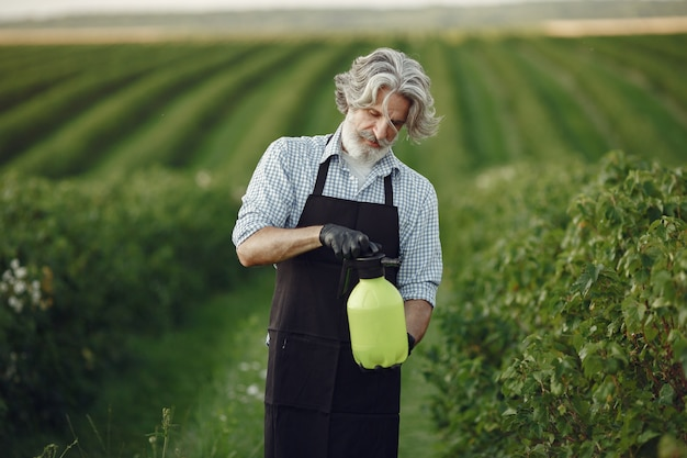 Rolnik opryskujący warzywa w ogrodzie herbicydami. mężczyzna w czarnym fartuchu.