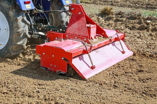 Rolnik orze pole. mały traktor z pługiem w polu. uprawa.