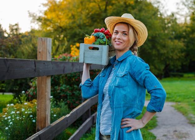 Rolnik piękna kobieta w kapeluszu z pudełkiem świeżych ekologicznych warzyw w ogrodzie