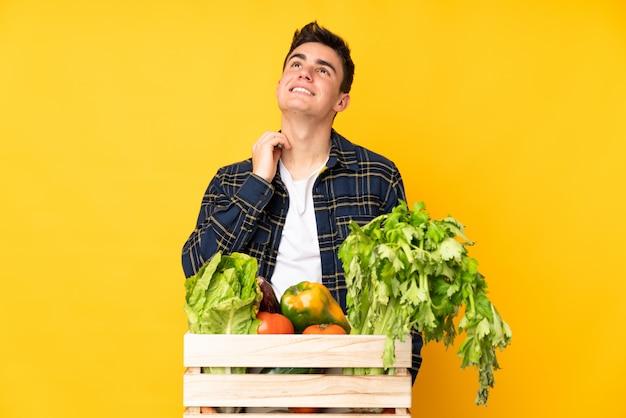 Rolnik posiadający kosz pełen świeżych warzyw
