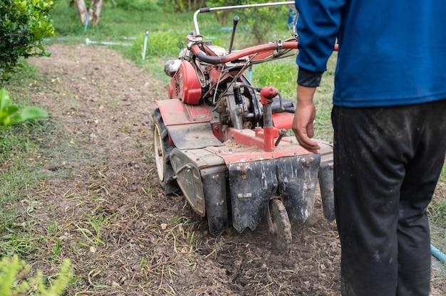 Rolnik prowadzący traktor odgarniający glebę na plantacji
