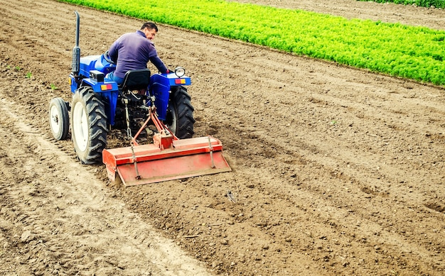 Rolnik prowadzi traktor z frezarką