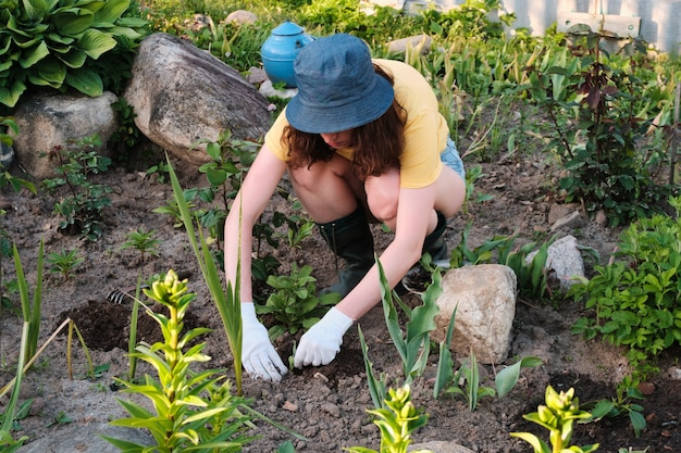 Rolnik sadzący roślinę w glebie.
