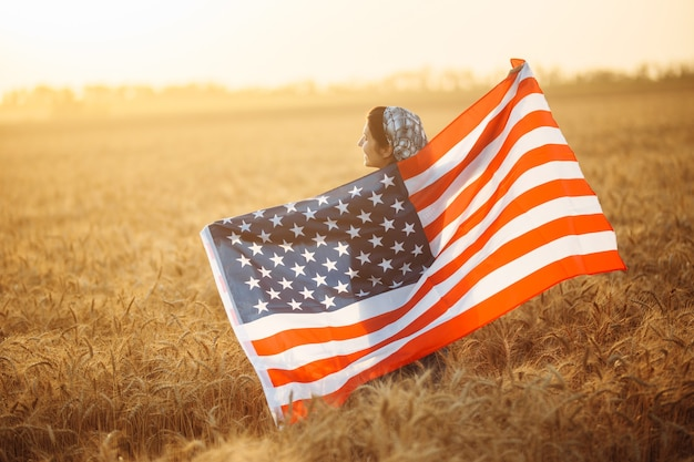 Rolnik stoi z amerykańską flagą na polu dojrzałej pszenicy na tle pięknego zachodu słońca. flaga powiewa na wietrze. letni krajobraz.