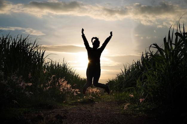 Rolnik sylwetka kobiety skacze na plantacji trzciny cukrowej w tle zachód słońca wieczór