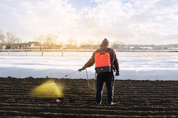 Rolnik traktuje pole z chwastów i trawy pod uprawę ziemniaków używaj środków chemicznych w rolnictwie