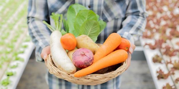 Rolnik trzyma kosz ekologicznych warzyw. warzywa ekologiczne z gospodarstw, które są gotowe do eksportu od rolników.