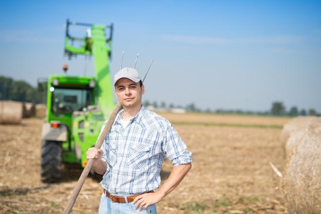 Rolnik trzyma widły w swoim polu