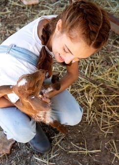 Rolnik trzymający małą kozę