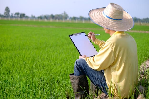 Rolnik ubrany w żółtą koszulę z długimi rękawami siedzi na polu trzymając tabliczkę z czystym papierem.