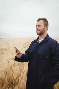 Rolnik używa telefon komórkowego w polu