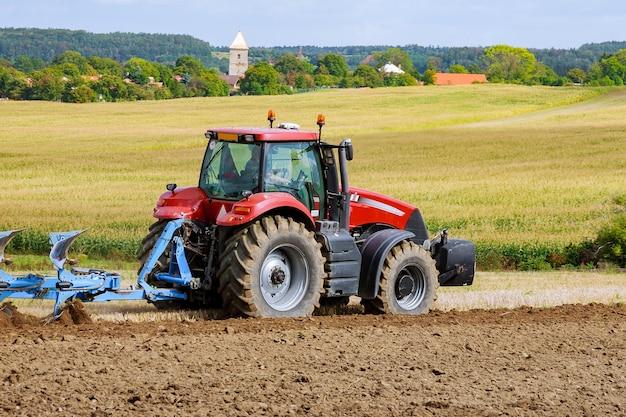 Rolnik w czerwonym ciągniku przygotowujący ziemię pługiem do siewu