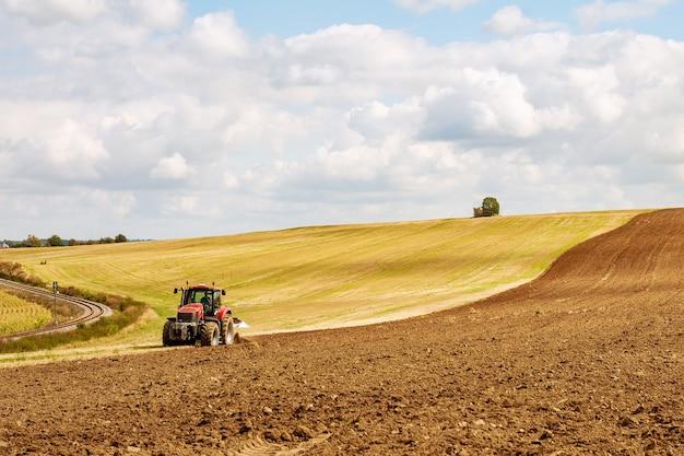 Rolnik w czerwonym traktorze przygotowuje ziemię z pługiem do siewu