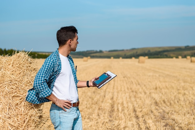 Rolnik w dżinsach i koszuli z tabletem w ręku jest w polu