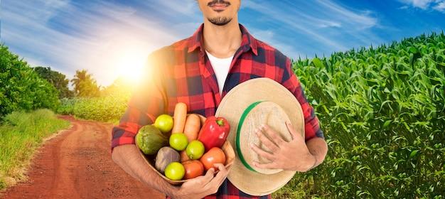 Rolnik w kapeluszu trzyma kosz warzyw w gospodarstwie uprawnym. pracownik rolny w polu.