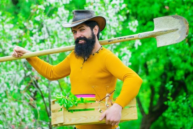 Rolnik w ogrodzie wiosną. ogrodnik z narzędziami ogrodniczymi. sadzenie człowieka z łopatą.