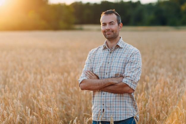 Rolnik w polu pszenicy o zachodzie słońca