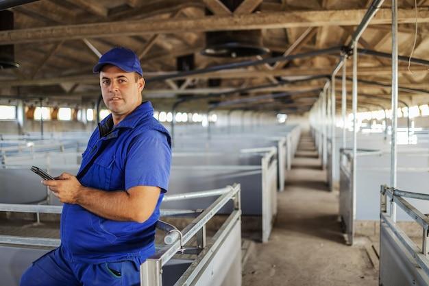 Rolnik w stojącej i pochylonej odzieży roboczej. używa smartfona do dzwonienia do dystrybutora zwierząt