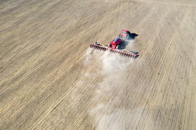 Rolnik w traktorze przygotowuje ziemię kultywatorem do siewu.