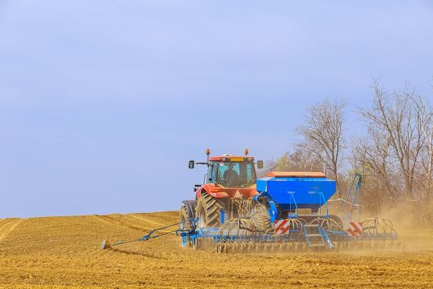 Rolnik z siewnikiem na ciągniku - siew zboża na polu rolniczym. uprawa pszenicy.