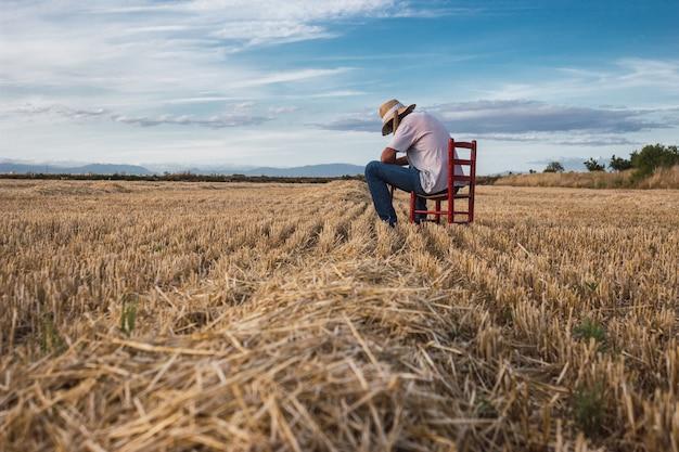 Rolnik ze słomianym kapeluszem i motyką siedzi na czerwonym krześle na środku pola. koncepcja rolnictwa.