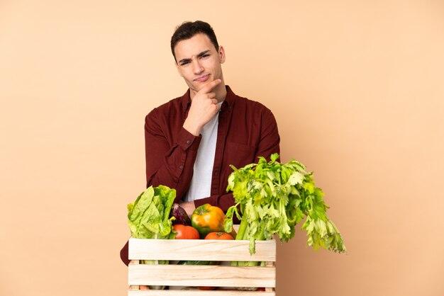 Rolnik ze świeżo zebranych warzyw w pudełku na beżowym myśleniu na ścianie