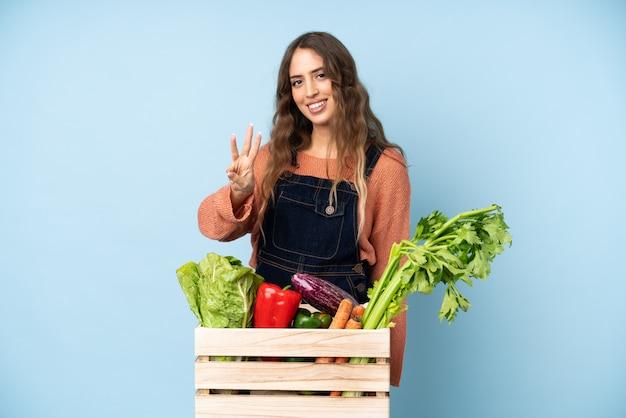 Rolnik ze świeżo zebranych warzyw w pudełku szczęśliwy i licząc trzy z palcami
