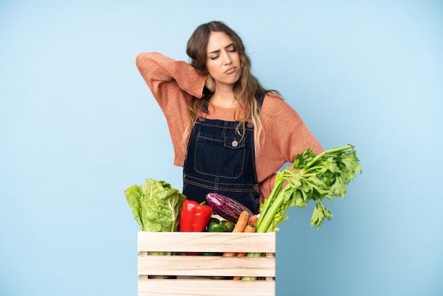 Rolnik ze świeżo zebranych warzyw w pudełku z bólem szyi
