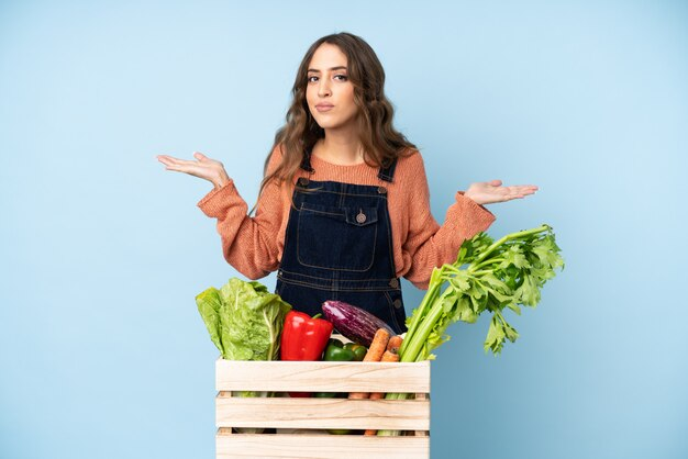 Rolnik ze świeżo zebranymi warzywami w pudełku mającym wątpliwości podczas podnoszenia rąk