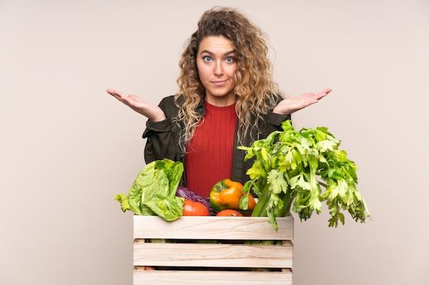 Rolnik ze świeżo zebranymi warzywami w pudełku na beżowym tle, który ma wątpliwości i zdezorientowany wyraz twarzy