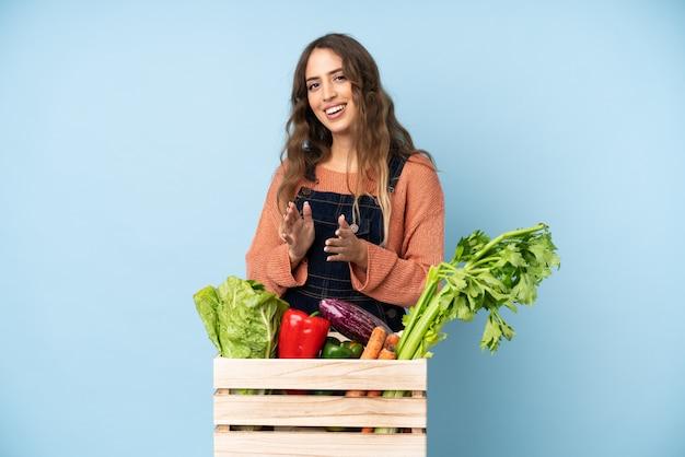 Rolnik ze świeżo zebranymi warzywami w pudełku oklaskującym po prezentacji na konferencji
