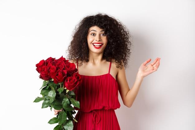 Romans i walentynki. kobieta dysząc zaskoczona i szczęśliwa, otrzymuje prezent niespodziankę od kochanka, trzymającego bukiet czerwonych róż, stojącego na białym tle.