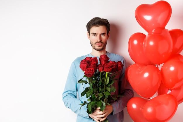 Romans na walentynki. przekonany, młody człowiek trzyma bukiet czerwonych róż, stojąc w pobliżu balonów serca, idąc na romantyczną randkę z kochankiem, białe tło