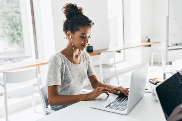 Romantyczna afrykańska kobieta z modną fryzurą siedzi w miejscu pracy i analizuje dane. kryty portret czarnej studentki pracującej z laptopem przed egzaminem.
