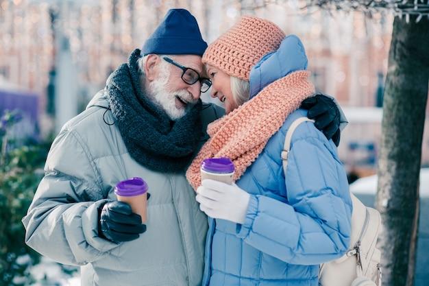 Romantyczna atmosfera starszego mężczyzny delikatnie przytulającego swoją żonę na świeżym powietrzu, pijąc z nią kawę w zimowy dzień