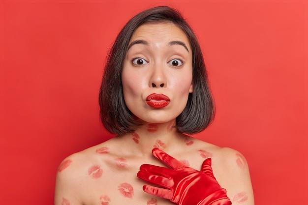 Romantyczna azjatka wysyła pocałunek w aparacie, ma zaokrąglone, pomalowane na czerwono usta, ma delikatne pozy z nagim ciałem, zdrowa skóra, nosi eleganckie, długie rękawiczki