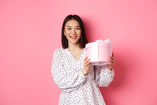 Romantyczna azjatycka kobieta w ślicznej sukience trzymającej pudełko z prezentem uśmiechnięta szczęśliwa do kamery stojącej z pres...