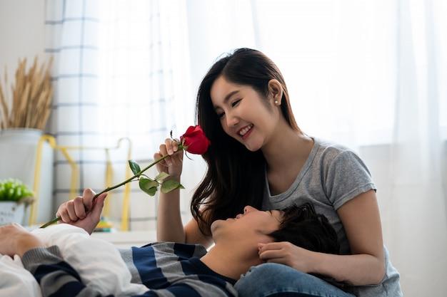 Romantyczna azjatycka para w sypialni, mężczyzna podający różę pięknej kobiecie i oboje pięknie całujący