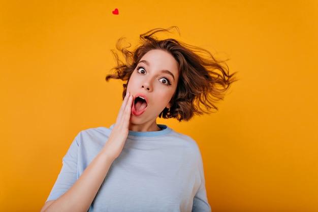 Romantyczna biała dziewczyna w niebieskiej koszulce bawi się podczas sesji zdjęciowej