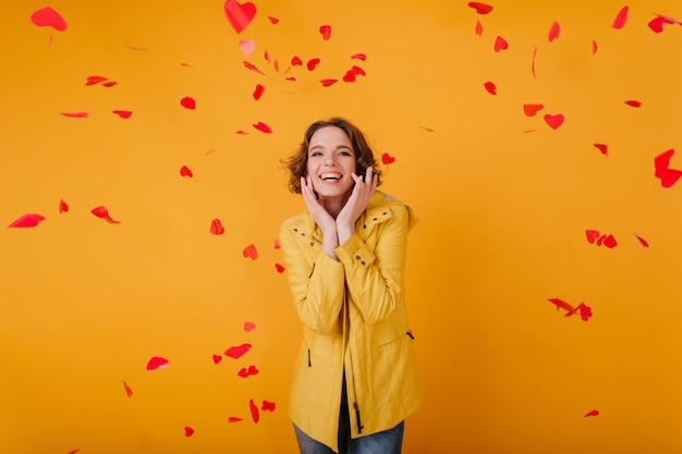 Romantyczna biała dziewczyna z ładny wyraz twarzy z czerwonymi sercami. kryty zdjęcie młodej kobiety kręcone obchodzi walentynki z uśmiechem.