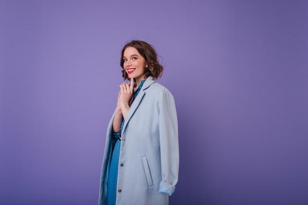 Romantyczna biała kobieta w eleganckim płaszczu figlarnie pozuje na fioletowej ścianie. kryty zdjęcie radosnej kręconej modelki z krótką fryzurą.