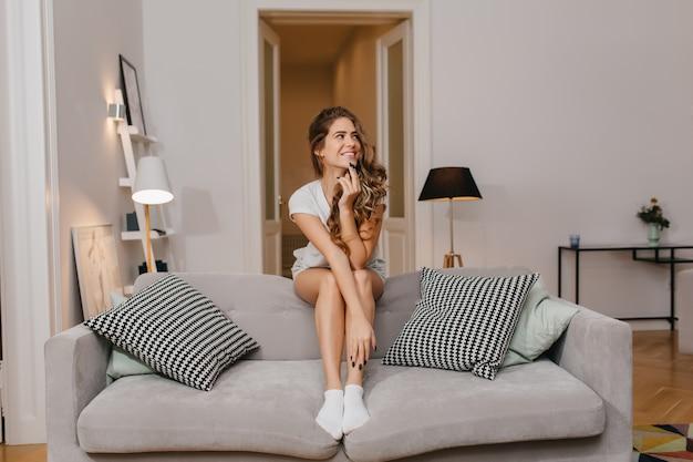 Romantyczna biała kobieta w uroczych skarpetkach siedzi między poduszkami i odwraca wzrok