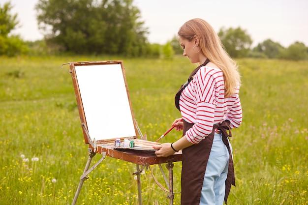 Romantyczna blond kręcone artystki w białej swobodnej koszuli w czerwone paski