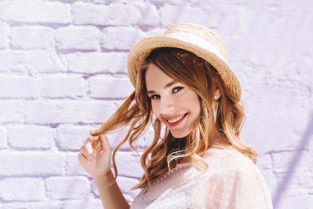 Romantyczna blondynka o pięknych oczach szczęśliwa, uśmiechnięta i dotykająca jej jasne włosy