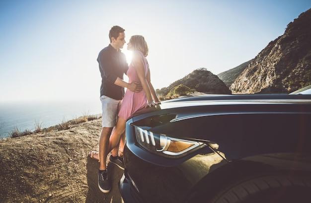 Romantyczna chwila na klifie w malibu. para ogląda panoramę z samochodu