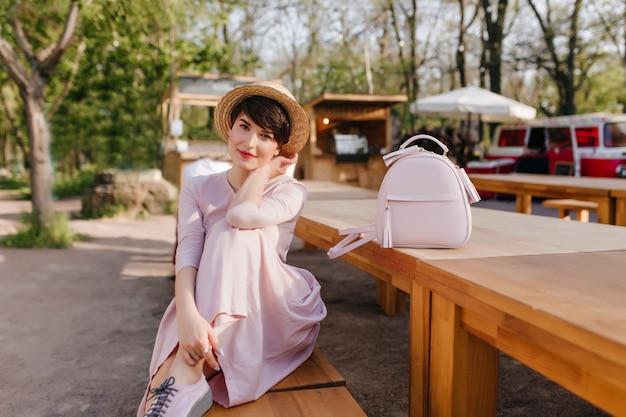 Romantyczna ciemnowłosa dziewczyna w ślicznej sukience przyjechała na piknik i czekała na przyjaciół