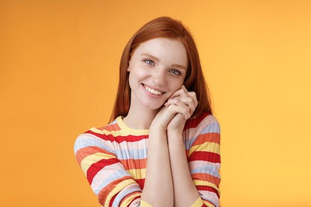 Romantyczna czuła, zmysłowa atrakcyjna, uśmiechnięta ruda dziewczyna topniejąca serce czuć ciepło zachwycona szczupłe dłonie szczerzą się radośnie słodki delikatny prezent stojący zadowolony pomarańczowe tło radość wdzięczna.